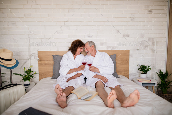 Senior couple on holiday in bathrobe on bed indoors in hotel room, drinking wine - Stock Photo - Images