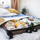 Open suitcase packed for holiday on bed at home, coronavirus concept - PhotoDune Item for Sale