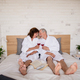 Senior couple on holiday in bathrobe on bed indoors in hotel room, drinking wine - PhotoDune Item for Sale