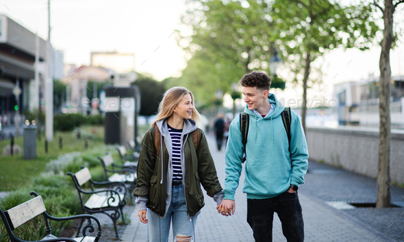 Happy young couple travelers in city on holiday, walking and talking - Stock Photo - Images