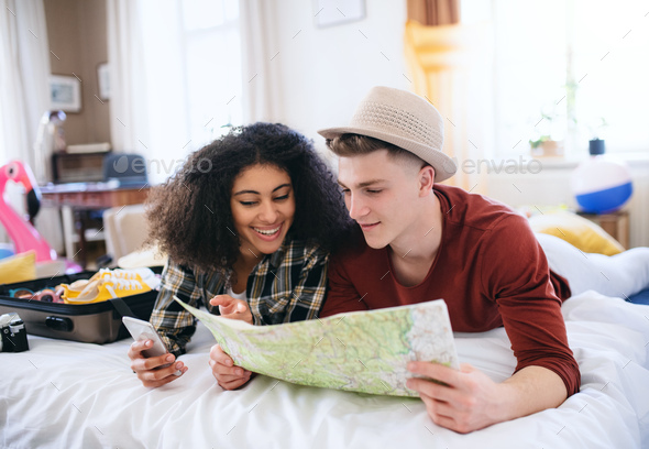 Cheerful young couple preparing and packing for summer holiday at home, planning - Stock Photo - Images