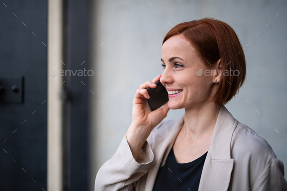Portrait of mid adult businesswoman standing indoors in office, using smarpthone - Stock Photo - Images
