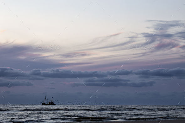 fishing ship in sea and sunset sky - Stock Photo - Images