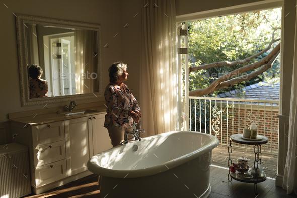 Senior caucasian woman running a bath in bathroom - Stock Photo - Images