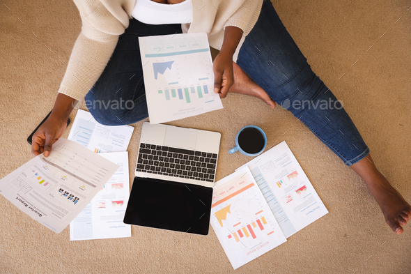 Happy african american woman working in bedroom, sitting floor using laptop and holding paperwork - Stock Photo - Images