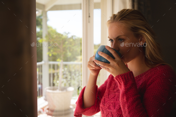Thoughtful caucasian woman standing by sunny balcony window drinking coffee - Stock Photo - Images