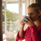 Thoughtful caucasian woman standing by sunny balcony window drinking coffee - PhotoDune Item for Sale