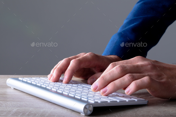 Close up of caucasian businessman typing on keyboard, isolated on grey background - Stock Photo - Images