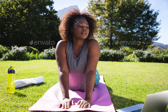 African american woman exercising on yoga mat in sunny garden - Stock Photo - Images