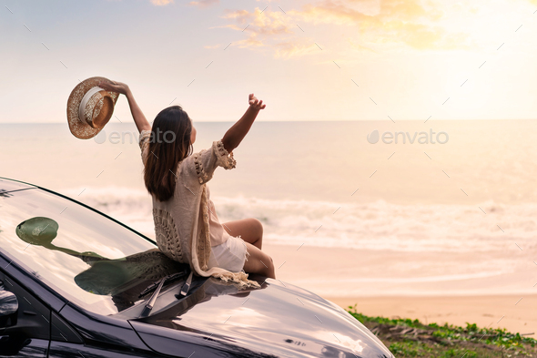 Young woman traveler sitting on a car and looking a beautiful sunset at the beach - Stock Photo - Images