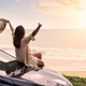 Young woman traveler sitting on a car and looking a beautiful sunset at the beach - PhotoDune Item for Sale