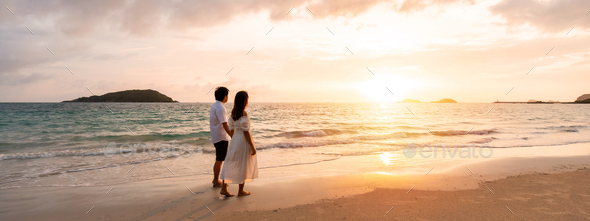 Young woman traveler holding man's hand and looking beautiful sunset on the beach - Stock Photo - Images