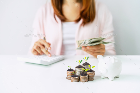 Young woman calculating expenses with stack of coins and piggy bank - Stock Photo - Images