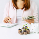 Young woman calculating expenses with stack of coins and piggy bank - PhotoDune Item for Sale