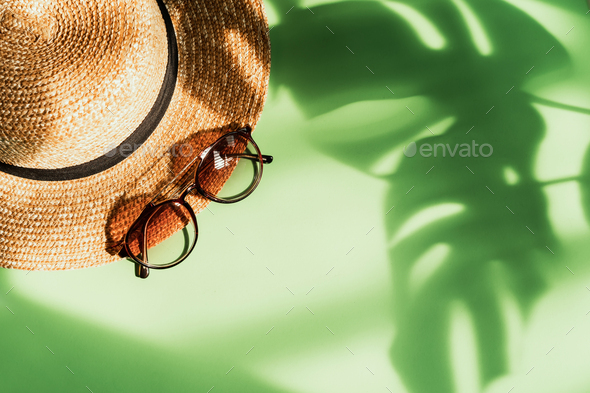 Hat and sunglasses with shadow of tropical green leave on color background - Stock Photo - Images