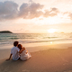 Young asian couple looking beautiful sunset on the tranquil beach, Summer vacation concept - PhotoDune Item for Sale