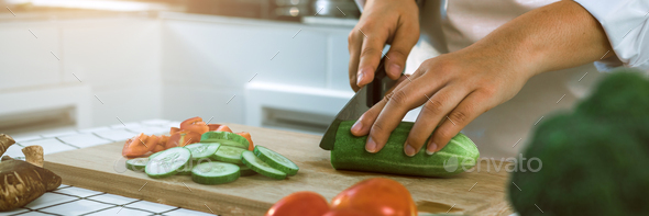 Woman using knife and hands cutting cucumber on wooden board in kitchen room. - Stock Photo - Images