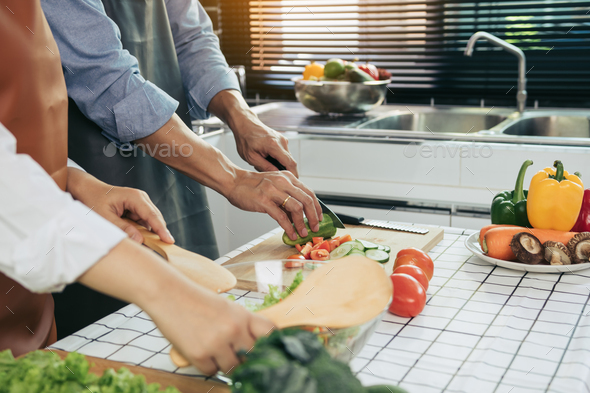 Two young asian couples are helping each other and enjoying cooking in the kitchen. - Stock Photo - Images