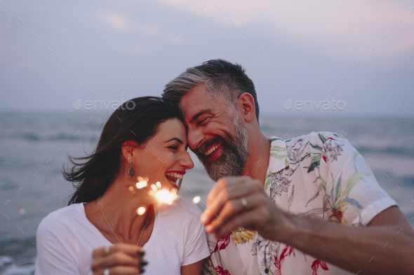 Couple celebrating with sparklers at the beach - Stock Photo - Images