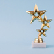 Three star awards for leader and ranking. Golden shiny prize on a pastel blue background. - PhotoDune Item for Sale