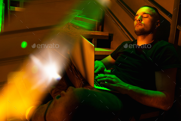 Cinematic portrait of handsome young man in neon lighted room, stylish male model indoors - Stock Photo - Images