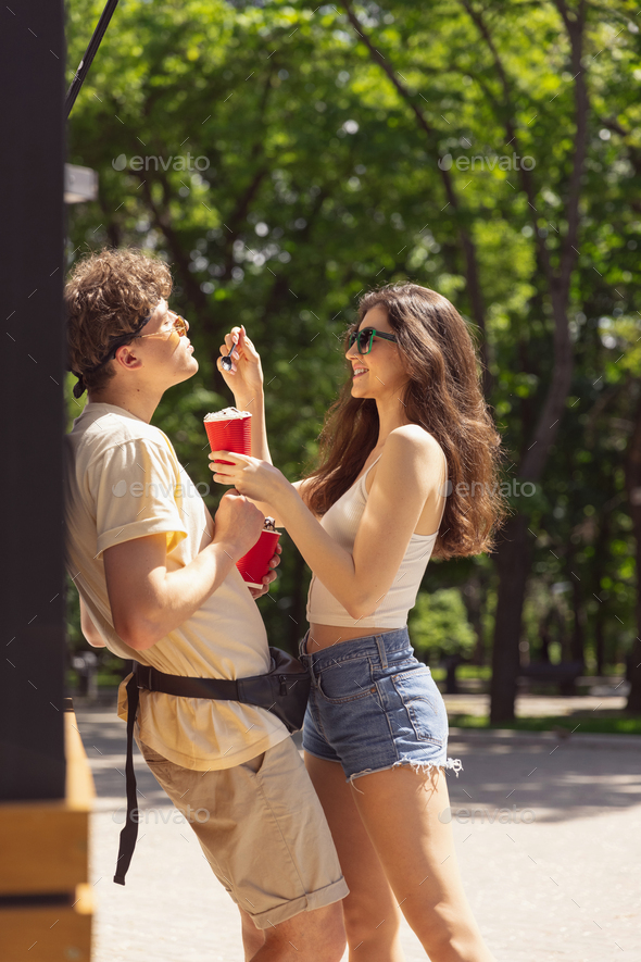 Happy attractive young couple romantically eating a fresh pizza outdoors - Stock Photo - Images