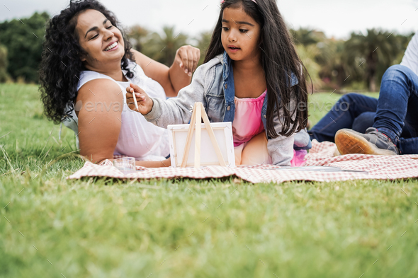 Happy indian family having fun painting with children outdoor at city park - Main focus on girl face - Stock Photo - Images