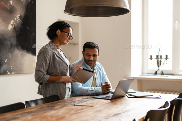 Middle eastern man and woman using laptop while working together - Stock Photo - Images
