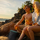 Young Couple Holding Beer Sitting On Rocks in the sunset at beach - PhotoDune Item for Sale