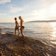 Beautiful couple holding hands and walks at the sea shore in the evening - PhotoDune Item for Sale