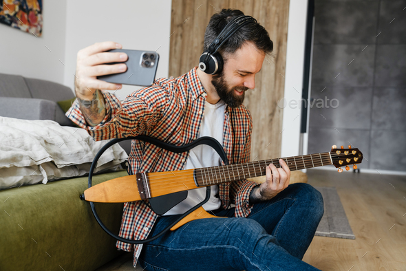 Smiling mid aged brunette bearded man playing - Stock Photo - Images