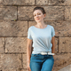 Women wearing t-shirt and jeans stays near a wall - PhotoDune Item for Sale