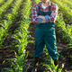 Middle age male caucasian confident satisfied farm worker with crossed arms stands at corn field - PhotoDune Item for Sale