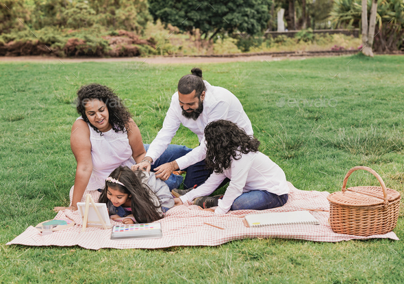 Happy indian family enjoy day outdoor while painting together - Family, parents and children love - Stock Photo - Images