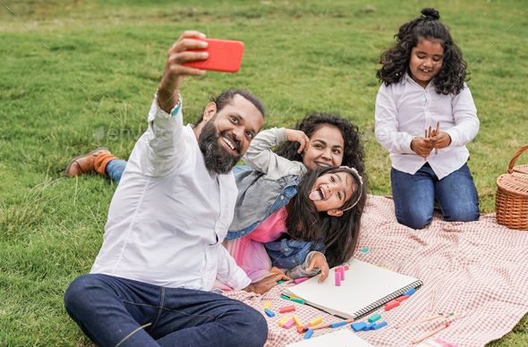 Happy indian family enjoy day outdoor at city park with pic nic and toys while taking a selfie - Stock Photo - Images