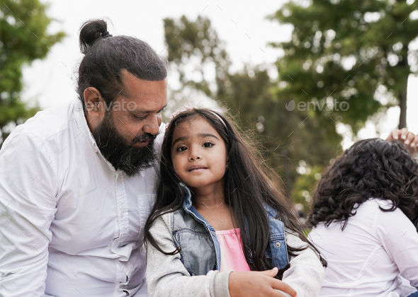 Indian family enjoy day at city park - Child sitting next to his father and looking in camera - Stock Photo - Images