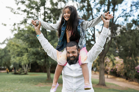 Indian father and child having playful time at city park - Family love concept - Stock Photo - Images