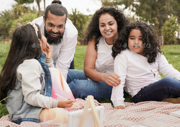 Happy indian family enjoy day outdoor with picnic while painting together - Stock Photo - Images
