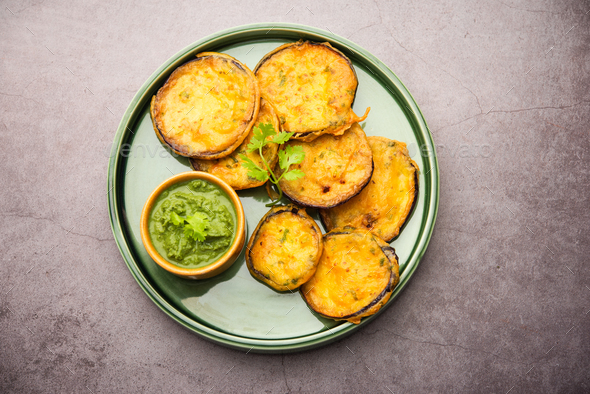 Tasty Brinjal Pakora or crispy eggplant fritters, Indian tea time snack served with green chutney - Stock Photo - Images
