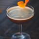 dark cocktail garnished with an orange twist on a dark bar setting - PhotoDune Item for Sale