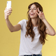 Positive charisamtic happy young girl curly-haired raise smartphone taking selfie show peace victory - PhotoDune Item for Sale