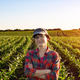 Middle age female caucasian smiling farm worker with crossed arms stands at corn field - PhotoDune Item for Sale