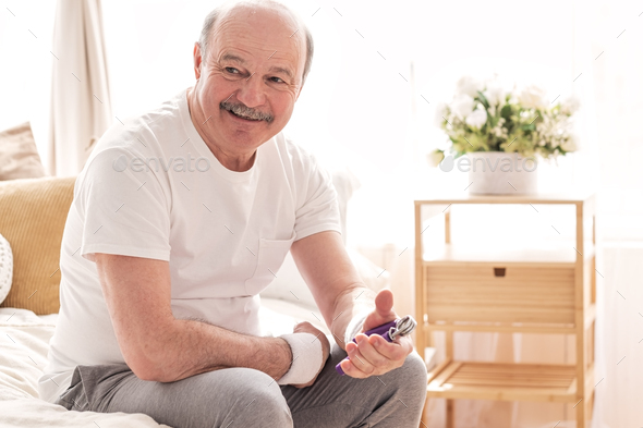 Senior hispanic positive man training his arm with hand expander at home - Stock Photo - Images