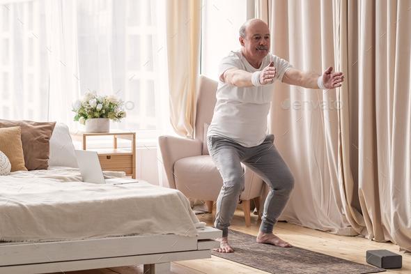 Senior hispanic man practicing yoga at home doing Chair pose, Utkatasana - Stock Photo - Images