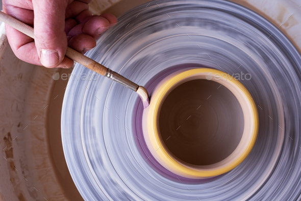 View on male hand holding a brush, painting on a ceramic using potter wheel. - Stock Photo - Images