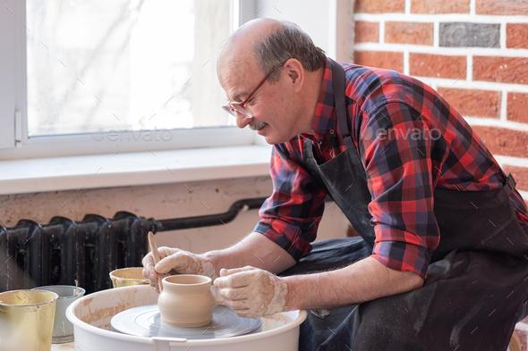 Senior male potter creating bowl in pottery workshop. Hobby at old age. - Stock Photo - Images