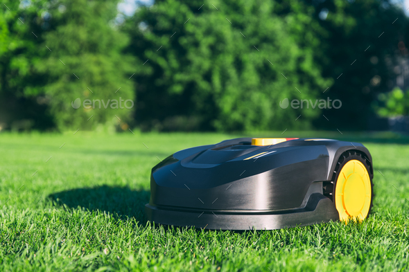 Robotic Lawn Mower cutting grass in the garden. - Stock Photo - Images