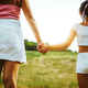 Hands of mother and daughter holding each other on field - PhotoDune Item for Sale