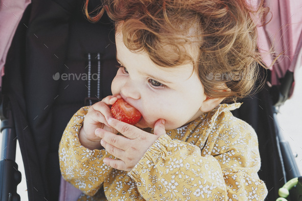Little baby girl eating a strawberry - Stock Photo - Images