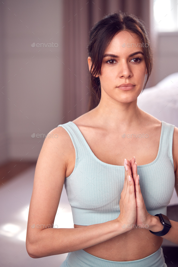 Woman Doing Yoga Wearing Fitness Clothing And Activity Monitor Sitting On Floor In Bedroom At Home - Stock Photo - Images
